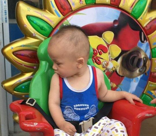 Kleines Kind sitzt im bunten Kinderstuhl