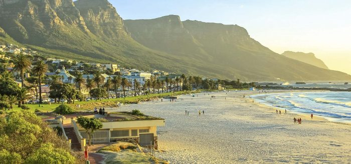 White long and spectacular beach of Camps Bay with Table Mountain National Park behind him in Cape Town, South Africa, Atlantic Ocean view. Shot taken at sunset.
